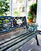 Vintage garden bench with peeling paint and ornate cast iron backrest outside greenhouse