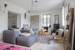 Grauer Polstersessel mit passendem Hocker und Retro Sessel um Beistelltische im Wohnbereich, gemusterte Teppiche auf Fliesenboden