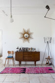 Exotic wood sideboard below sunburst mirror and various lamps on walls and ceiling