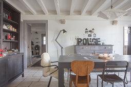 Grauer Esstisch mit Retro Stühlen und grau Anrichte im Esszimmer mit Holzbalkendecke
