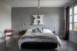 Felldecke auf Bett vor grauer Stuccolustrowand mit weissem Deko-Buchstabe