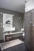 Badezimmer mit weissem Waschtischelement und eingebautem Schrank mit Metalltüren