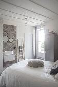 Bett mit weisser Tagesdecke und Waschtisch vor gefliester Wand mit grauen Ornamentfliesen in restauriertem Schlafzimmer