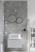 Modernes weißes Waschbecken mit Unterschrank an Wandstreifen mit grauen Ornamentfliesen