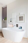 Free-standing bathtub below gallery of pictures on wall