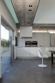 Open-plan kitchen, white classic shell chair and recessed spotlights in exposed concrete ceiling in modern house