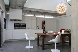 White shell chairs around rustic wooden table in open-plan kitchen with concrete ceiling
