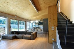 Staircase in open-plan, minimalist, designer living area with wooden ceiling