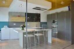 Kitchen counter in elegant minimalist designer kitchen seen through glass partition wall
