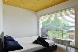 Minimalist bedroom with panoramic window and wooden ceiling