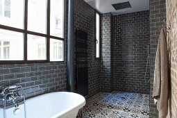 White bathtub below industrial window and shower area with ornate tiles