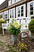 White garden bench, basket of apples and hydrangeas in zinc bucket outside country house with white windows
