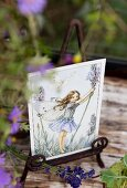 Romantic postcard of flower fairy on vintage metal stand decorated with lavender flowers