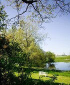 White garden bench on green lawn next to pond in rural surroundings