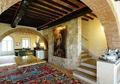 Mediterranes Wohnzimmer mit Steinwand und Balkendecke