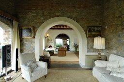Mediterranes Wohnzimmer mit Natursteinwand und Rundbögen