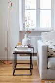 Delicate side tables and copper lamp next to sofa