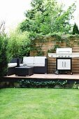 Lounge furniture and barbecue on raised terrace in garden