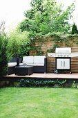 Erhöhte Terrasse im Garten mit Loungemöbeln und Grill