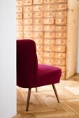 Red retro easy chair in hallway with apothecary cabinet against far wall