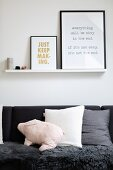 Framed prints on narrow shelf above sofa