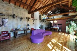 Curved purple sofa on wooden floor in converted loft apartment with wooden roof structure and gallery