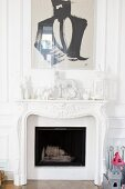 White figurines and painting above fireplace