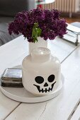 Lego-style skull pot in front of vase of lilac