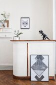 Artwork leaning against half-heigh wall with dinosaur figurine on bar above