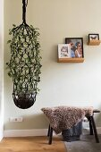 Large macrame plant next to stool covered in sheepskin blanket