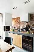 Woman and cat in modern kitchen with brick wall