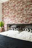 Bed with rustic headboard against brick wall in bedroom