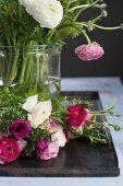 Glasvase mit Blumenstrauss aus Ranunkeln und Anemonen
