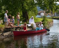Two woman in red canoe on river and children on bathing jetty on summer day