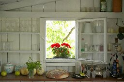 Red geraniums in open window in wooden wall, glasses on shelves and loaf of bread on kitchen worksurface