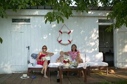 Two women and toddler on outdoor easy chairs below life belt on wall of white changing hut