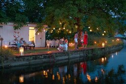 Romantic garden party at twilight; guests amongst torches and lanterns hung from trees