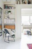 Classic metal mesh chair in front of open-fronted shelves in corner and mounted above door