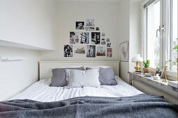 Double bed with grey scatter cushions against white-painted headboard below decorative arrangement of feminine fashion photos on white wall next to window