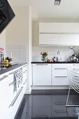 Wall-mounted cabinet and glossy black-tiled floor in white fitted kitchen