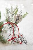 Wooden snowflake and sprig of fir in jam jar