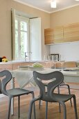 Set dining table and modern, grey plastic chairs in kitchen of renovated country house