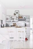Offene Küche mit weisser Küchenzeile, Wandfliesen und Küchentheke