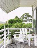 Überdachte Terrasse mit weißem Holzsessel im Landhausstil; Blick über Brüstungsgeländer auf Gartn