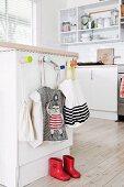 Kindergarderobe an Küchentheke mit Stofftaschen und roten Kindergummistiefeln auf Dielenboden