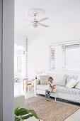 Kleines Mädchen an hellem Polstersofa in Wohnzimmer mit Kinderspielecke und bunter Girlande