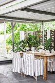 Überdachte Terrasse mit grau-weiß gestreiften Hussensesseln und Grünpflanzen vor Sichtschutzwand