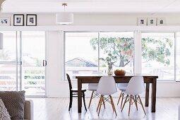 Offener Wohnbereich mit Holztisch und weissen Schalenstühlen vor Fensterfront und Bildergalerie unterhalb der Decke