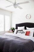 Schlafzimmer mit Decken-Ventilator, viele Kissen auf dem Bett