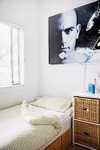 Corner of a room with a single bed in front of a window with blinds, bedside table and portrait poster
